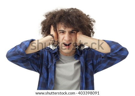 Furious young man covering ears with hands - stock photo