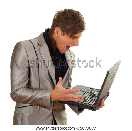 furious young man in grey suit keeping laptop