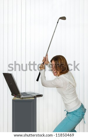 Furious young woman smashing a laptop computer with a golf club. - stock photo