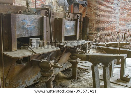 Furnaces and smithing tools inside brick blacksmith shop.