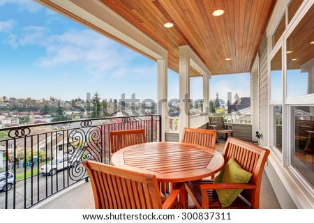 Furnished covered balcony with lights, and a view. - stock photo