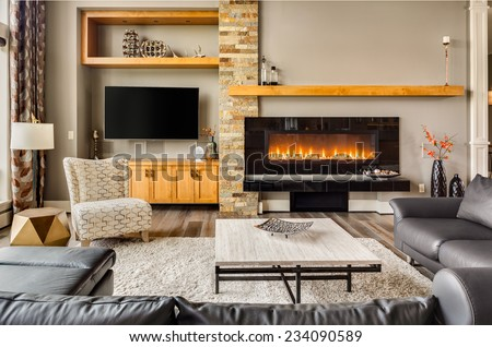Furnished living Room in Luxury Home with Roaring Fire in Fireplace - stock photo