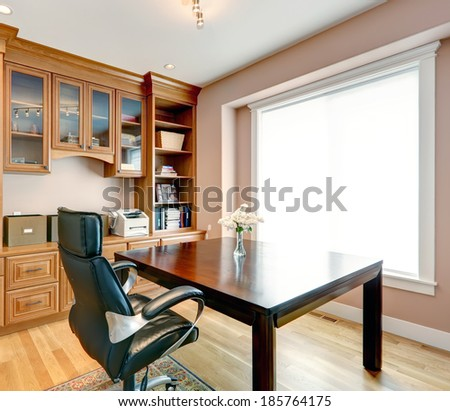 Furnished luxury living room with leather ottoman. View of fireplace with tv and built-in cabinet - stock photo