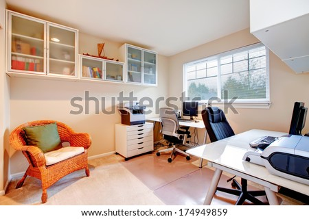 Furnished  office room with rustic wicker chair, glass door storage cabinets on the wall - stock photo