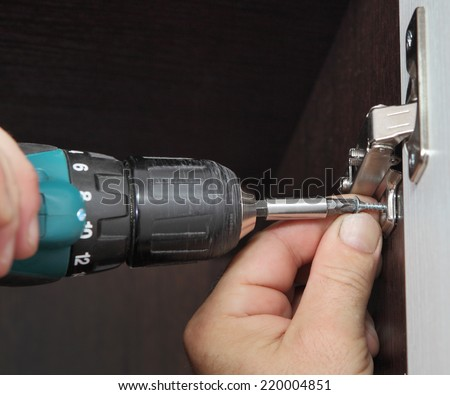 Furniture assembly, joiner mounts door hinges closet for clothes using cordless screwdriver. - stock photo