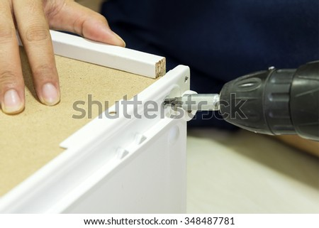 furniture assembly process by screw driver  - stock photo