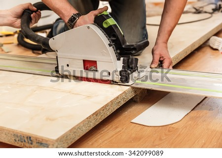 Furniture manufacturing inside working with the saw - stock photo