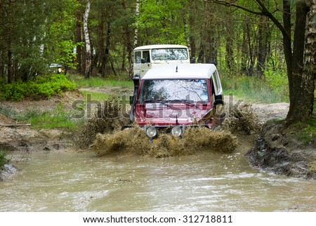 FURSTENAU, GERMANY - MAY 09, 2015: A Toyota is driving through a pond of water on a special off the road terrain for land cruisers and vehicles in Germany - stock photo