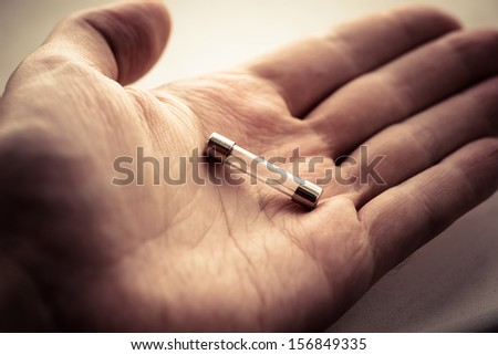 Fuse in human hand. Color toned image. - stock photo