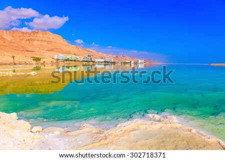 Fused salt made on the surface of the water. Emerald water of the Dead Sea - stock photo