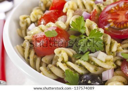Fusili pasta salad, with rocket pesto, juicy tomatoes, olives and onion. - stock photo