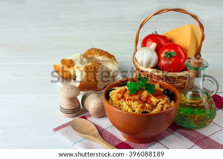 fusilli pasta and olives with parsley and ketchup in the plate near the wicker baskets with tomatoes and garlic with a glass  bottle of sunflower oil on wooden whitr background - stock photo
