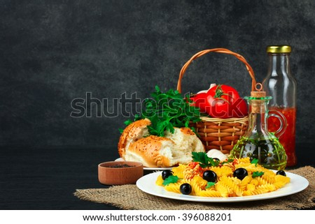 fusilli pasta and olives with parsley and ketchup in the plate near the wicker baskets with tomatoes and garlic with a glass  bottle of sunflower oil on wooden black background - stock photo