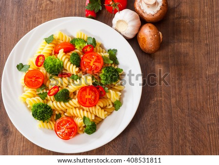 Fusilli pasta with cherry tomatoes and broccoli in a plate on wooden table - stock photo