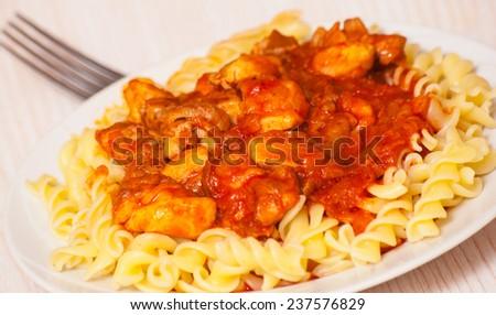Fusilli pasta with chicken in tomato sauce - stock photo