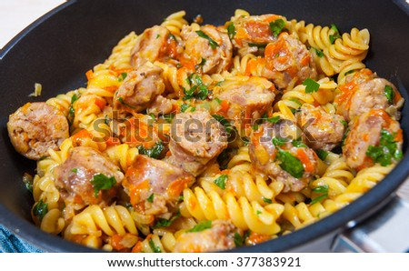 Fusilli pasta with sausage and vegetables in a frying pan - stock photo