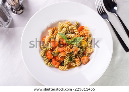 Fusilli pasta with tomatoes and zucchini served on the table - stock photo