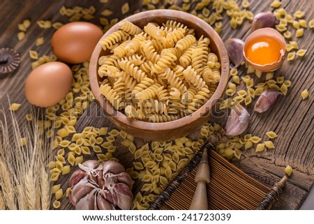 Fusilli raw pasta in bowl on rustic style