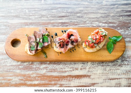 Fusion Mix Bruschetta, Italian Appetizer with Roasted tomatoes, Mozzarella cheese, Roasted beef and Parma Ham - stock photo