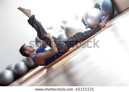 fusion of mind and body - man practicing  pilates - stock photo