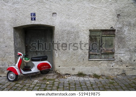 FUSSEN, GERMANY - OCTOBER 17, 2016: Motorbike parking in front of an old house in abandoned street in Fussen, Germany.