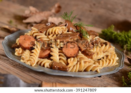 Fussili pasta with mushrooms and sausage - stock photo