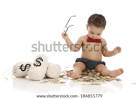 Future banker.  Adorable baby boy wearing a red bow-tie and sitting on a pile of gold coins next to money bags.  Isolated on white with room for your text. - stock photo