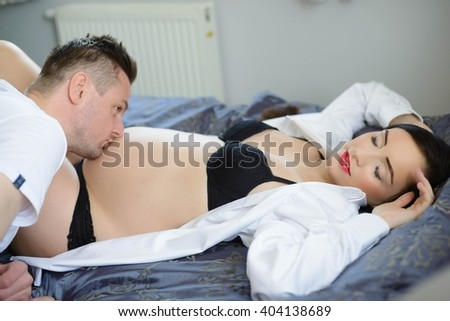 Future dad kissing the belly of his pregnant wife. A woman dressed in a white shirt and black lingerie lying on a bed - stock photo