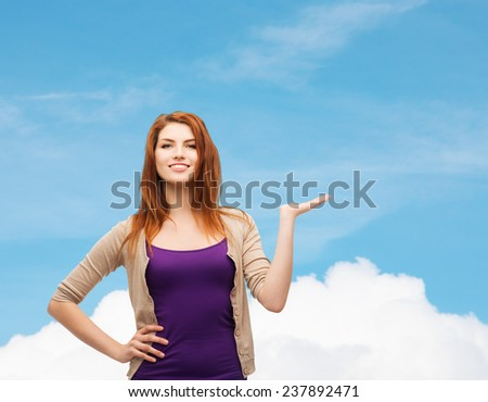 future, dream, advertising and people concept - smiling teenage girl in casual clothes holding something on her palm over blue sky and cloud background - stock photo