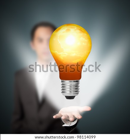 future eco - green energy concept, light bulb of solar energy in man hand - stock photo