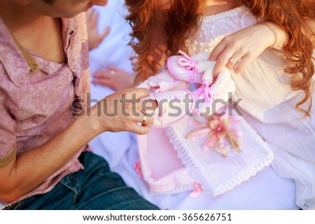 future father and mother waiting child young man holding his pregnant wife at belly baby shoes shoes for little princess young couple awaiting replenishment Family - stock photo
