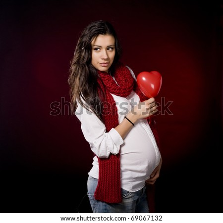 Future mommy holding heart - stock photo