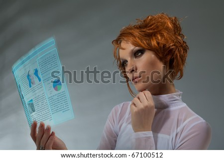 Future of IT - woman holding transparent flat monitor and browsing internet concept made with professional makeup and hair stylist