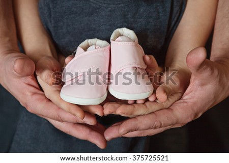 Future parents holding a pair of little shoes in their hands. Hands of parents and kid holding a pair of little shoes. Waiting for a new family member. Selective focus - stock photo