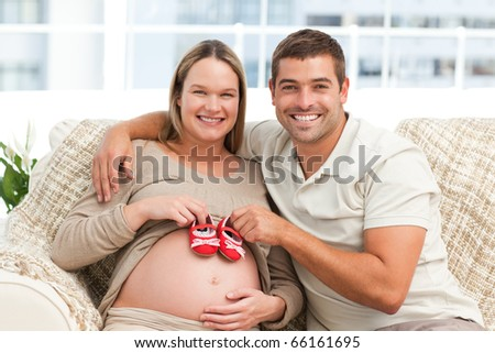 Future parents playing with baby shoes sitting on the sofa at home - stock photo