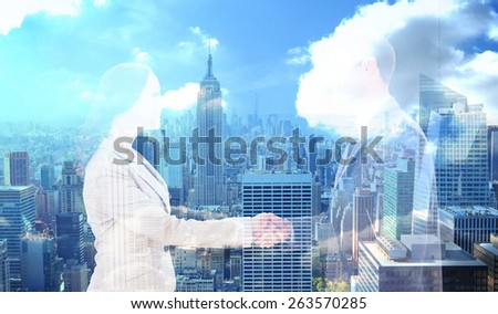 Future partners shaking hands against city skyline - stock photo