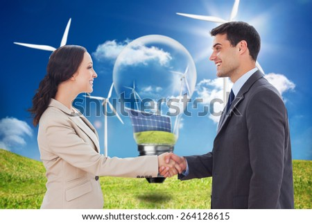 Future partners shaking hands against light bulb showing solar panels and turbines in a field with wind turbines - stock photo