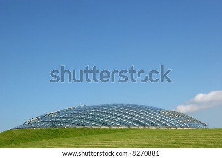 Futuristic conservatory made of glass panels and curved steel joists, set into a grass hillside with a clear blue sky to the rear. - stock photo