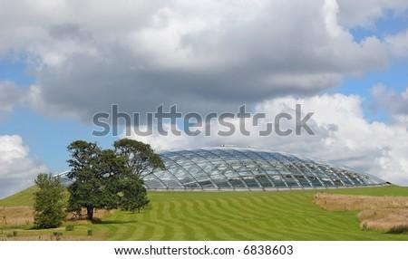 Futuristic eco dome made of glass panels set into a grass hillside. Location, National Botanical Gardens of Wales, United Kingdom. - stock photo