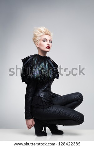 futuristic fashion model on a white reflective platform posing and looking at camera - stock photo