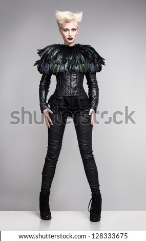 futuristic fashion model wearing leather clothes and a blouse made of feathers standing on a white platform and posing - stock photo