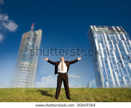Futuristic freedom - Happy business man standing on green grass - arms outstretched - stock photo