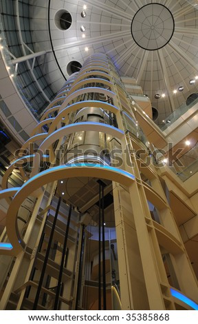 futuristic giant glass elevator going up inside of huge public building