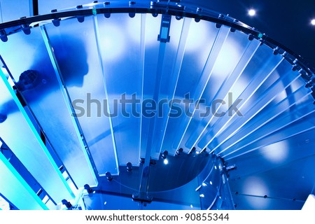 futuristic glass spiral staircase with modern building background in hongkong