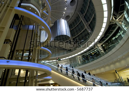 futuristic interior with moving escalator and many people on it, Tokyo Japan - stock photo