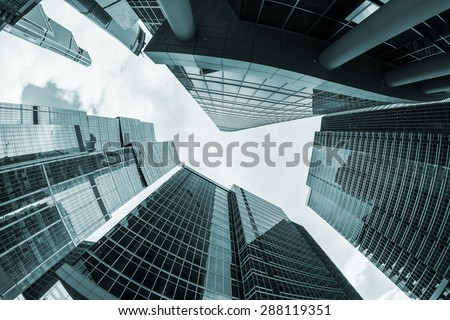 futuristic modern skyscrapers of glass and metal. Focus on the top of the building. toned photo - stock photo