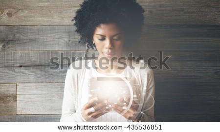 Futuristic technology and communication concept. Smiling pretty black girl with Afro hairstyle using digital tablet, checking email or typing a message. Visual effects. Worldwide connection interface - stock photo