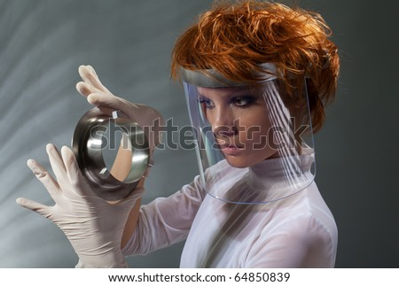 Futuristic woman examine metal detail holding it in latex gloves and wearing white clothes made with professional makeup and hair stylist