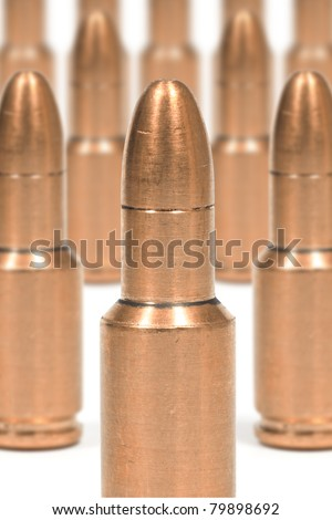 Fuzzy bullets in the background with a clear bullet in the foreground - stock photo