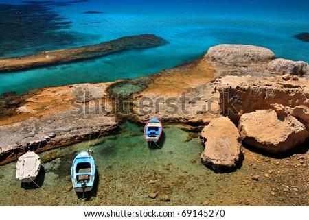 "Fyriplaka beach, Milos island, Greece. A natural rocky ""harbor"" with traditional fishing boats. - stock photo"